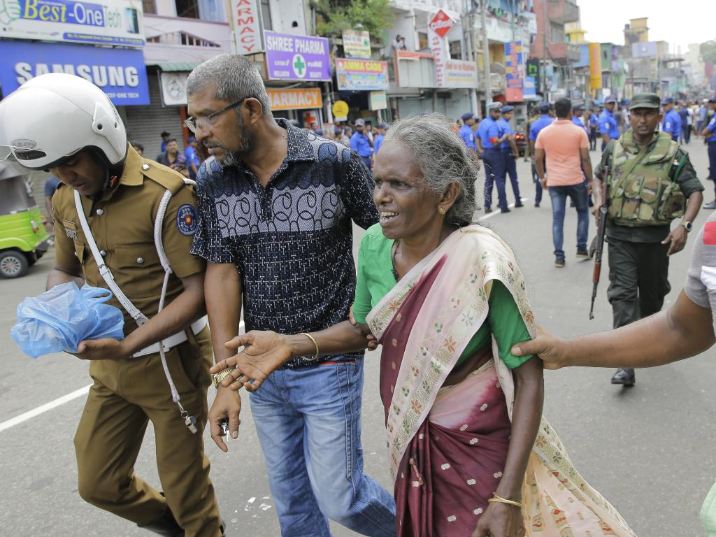 An elderly woman is helped near St. Anthony's Shrine after a blast in Colombo, Sri Lanka. Picture: AP