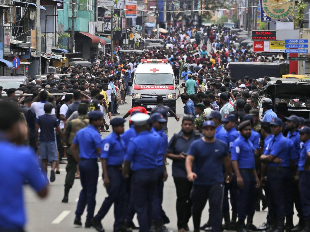 Sri Lankan police officers clear the road as an ambulance drives through carrying injured of Church blasts in Colombo, Sri Lanka. Picture: AP