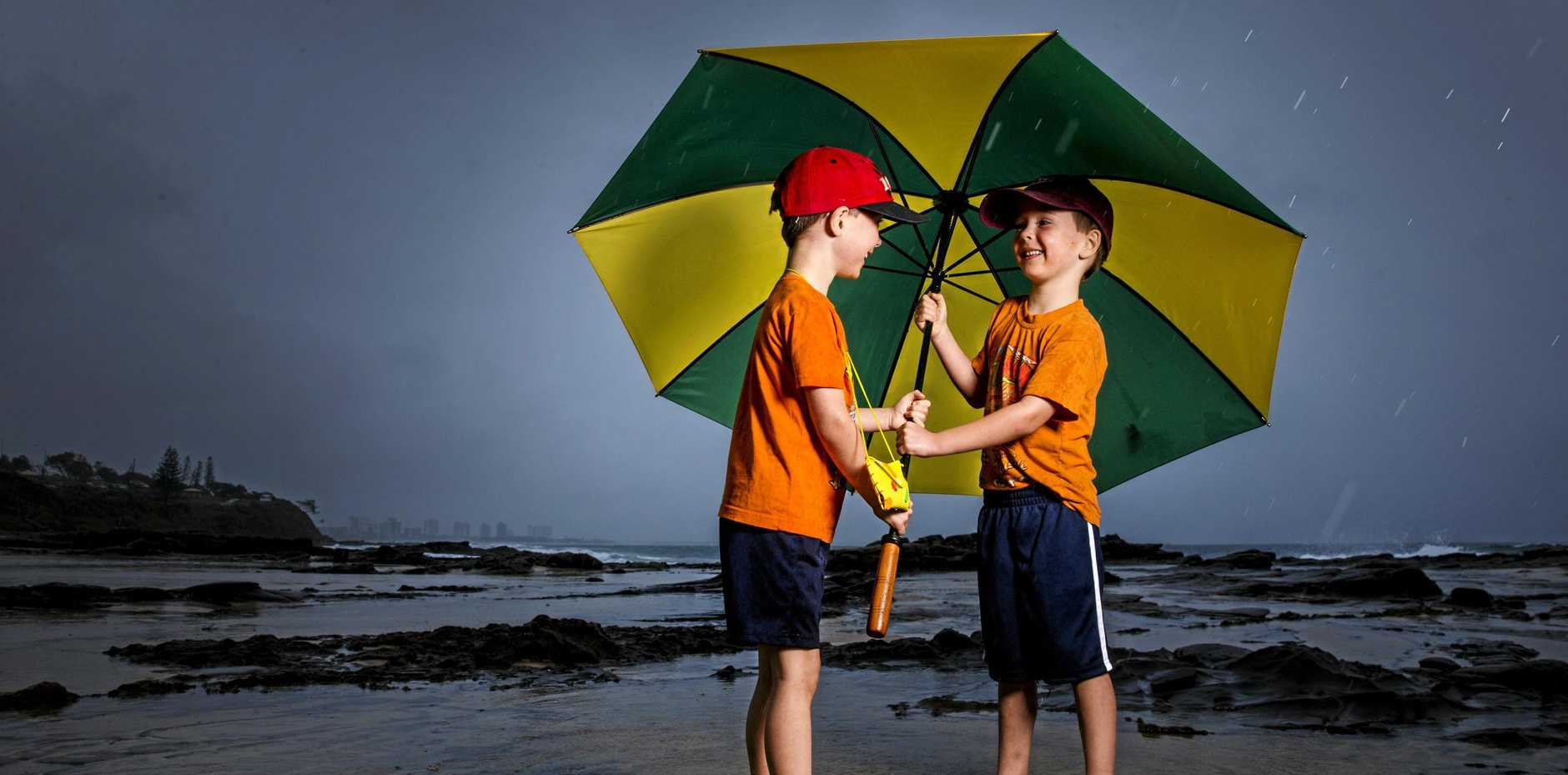 WET WEATHER: FIVE- year old twins Jacob and Timothy Booth from Canada didn't mind the rain at Mooloolaba as it was minus 30 degrees when they left home in Alberta, Canada for their Australian holiday as heavy falls were recorded across the Sunshine Coast.