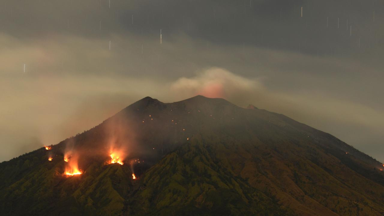 Trees burn on the slopes of Mount Agung volcano after it erupted on July 3, 2018. Picture: Sonny Tumbelaka