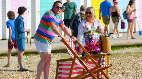 A man struggles to set up deckchairs on the beach to the amusement of his wife in Dorset. Picture: Graham Hunt/Alamy Live News