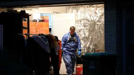 Police and forensics search the garage at the home in Minto. Picture: Damian Shaw