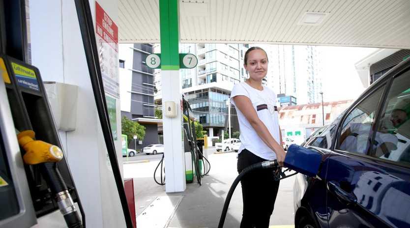 Nicole Dewe, from Tarragindi, fills up as experts warn of soaring fuel prices, (Image AAP/Steve Pohlner)