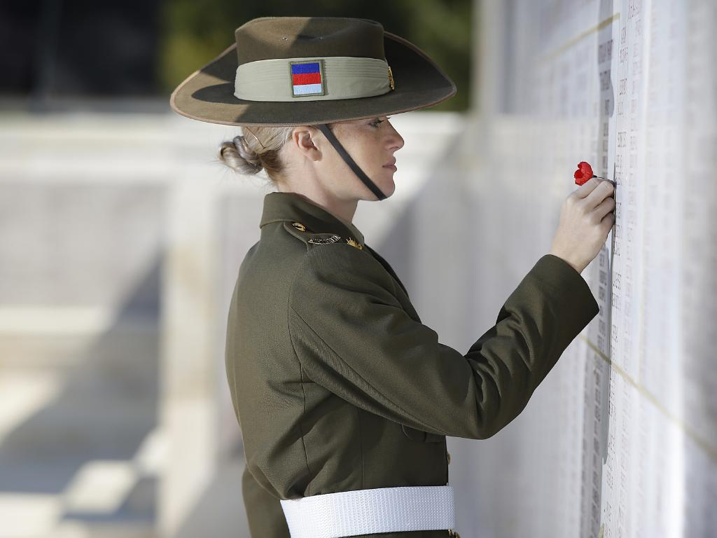 Private Hannah Bailey lays a poppy at the Lone Pine memorial wall dedicated to the missing. Picture: ADF