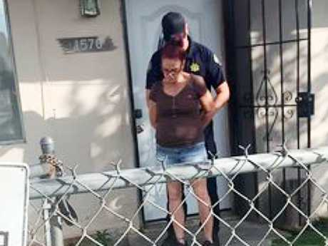 A handcuffed Culwell is led from her home in Coachella by an animal services officer. Picture: Riverside County Department of Animal Services