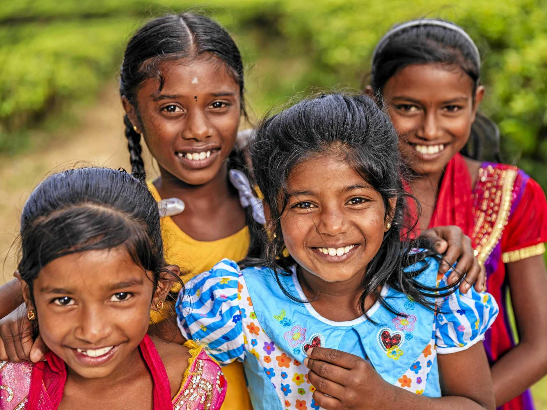 Sri Lankan young girls posing at a tea plantation. Their parents work on this tea plantation near Nuwara Eliya, Sri Lanka.