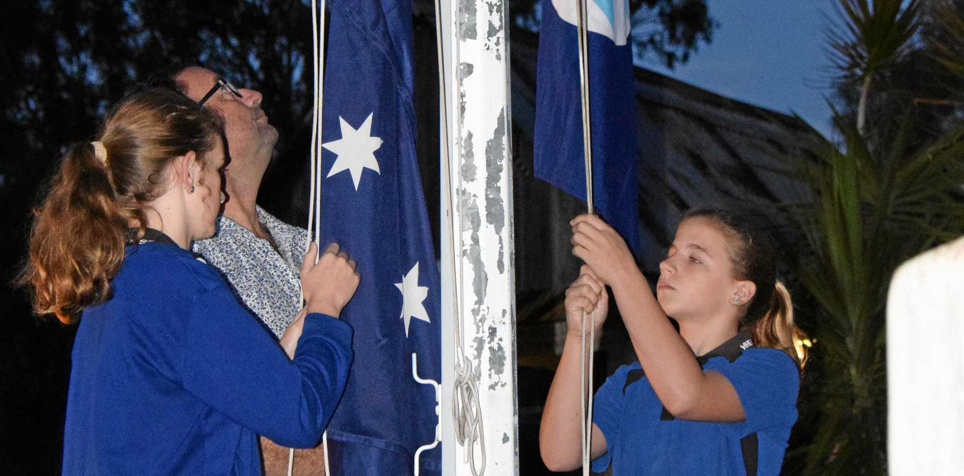 FLYING PROUDLY: Wheatlands principal Adam Head and students raise the flag at the Hivesville dawn service.