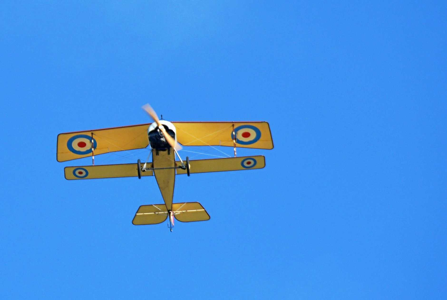 Pilot Jim Gollagher flies the Nieuport 11 replica of Major Stan Dallas' plane over the main streets of Nanango during the parade on April 25, 2019.