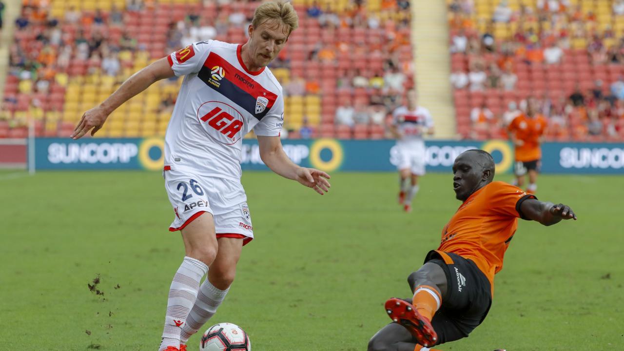 Adelaide United's Ben Halloran dribbles past Brisbane Roar's Ruon Tongyik. Picture: Glenn Hunt/AAP