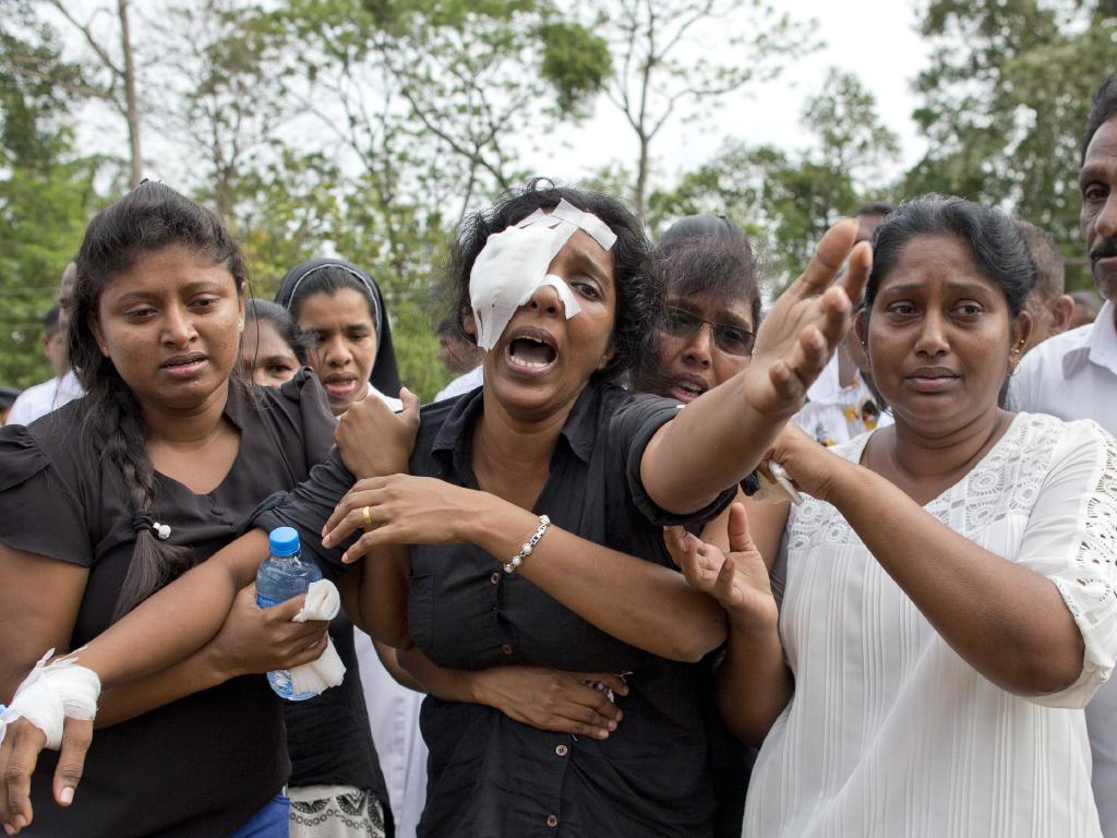 Anusha Kumari, center, weeps during a mass burial for her husband, two children and three siblings, victims of Easter Sunday's attacks in Sri Lanka. Picture: AP Photo