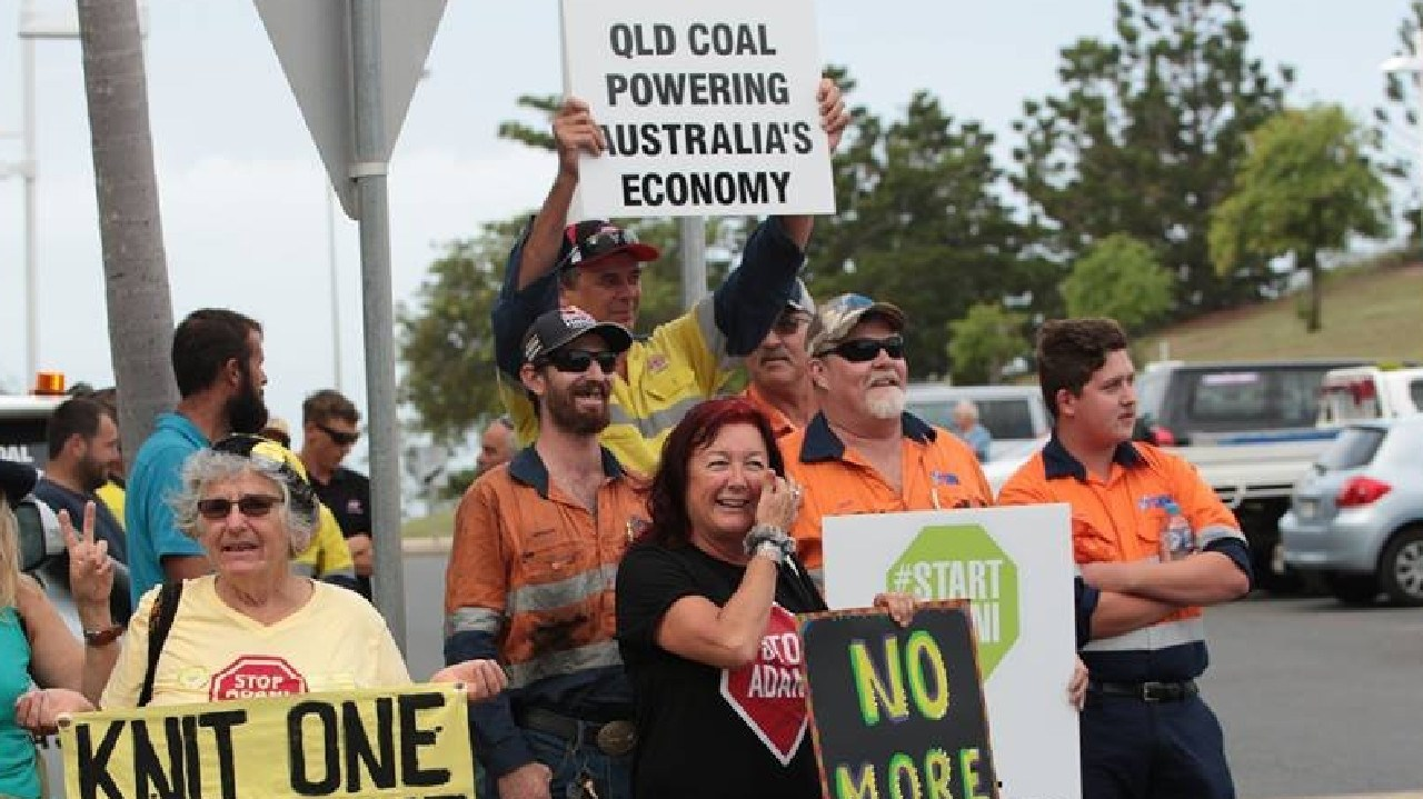 Counter protesters hold green #StartAdani and pro-coal placards during a protest against the company's Carmichael mine.