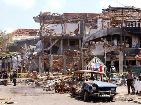 Forensic police officers and the wreckage of a car at the scene of the Sari Club nightclub blast in Kuta. Picture: AFP