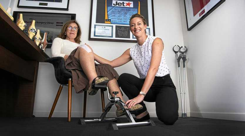 Janine Dickinson uses the stationary pedals a week after undergoing a total knee replacement, watched over by orthopaedic physiotherapist Larissa Sattler and Dr Christopher Vertullo of Bond University.