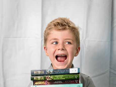 Elliot Ecklan, 6, with books by some of the authors appearing at the this year's Whitsunday Voices Youth Literature Festival.