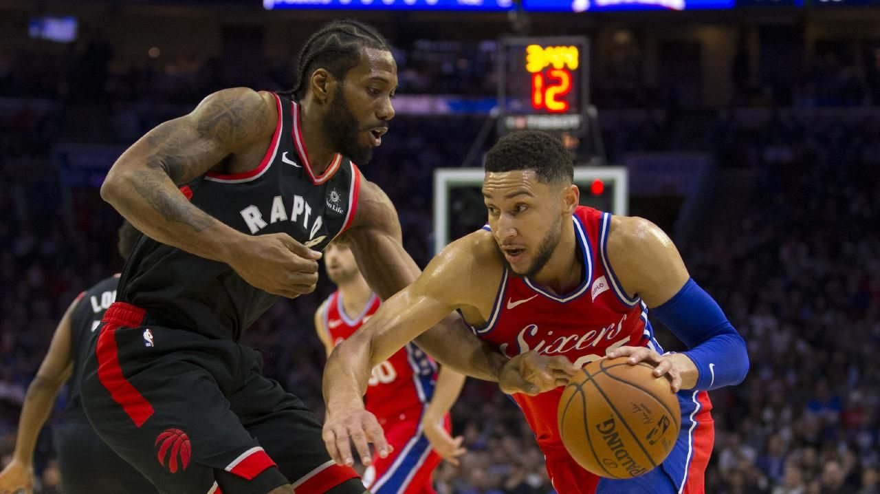 Kawhi Leonard pokes the ball away from Ben Simmons in a Raptors' win in February. (Photo by Mitchell Leff/Getty Images)