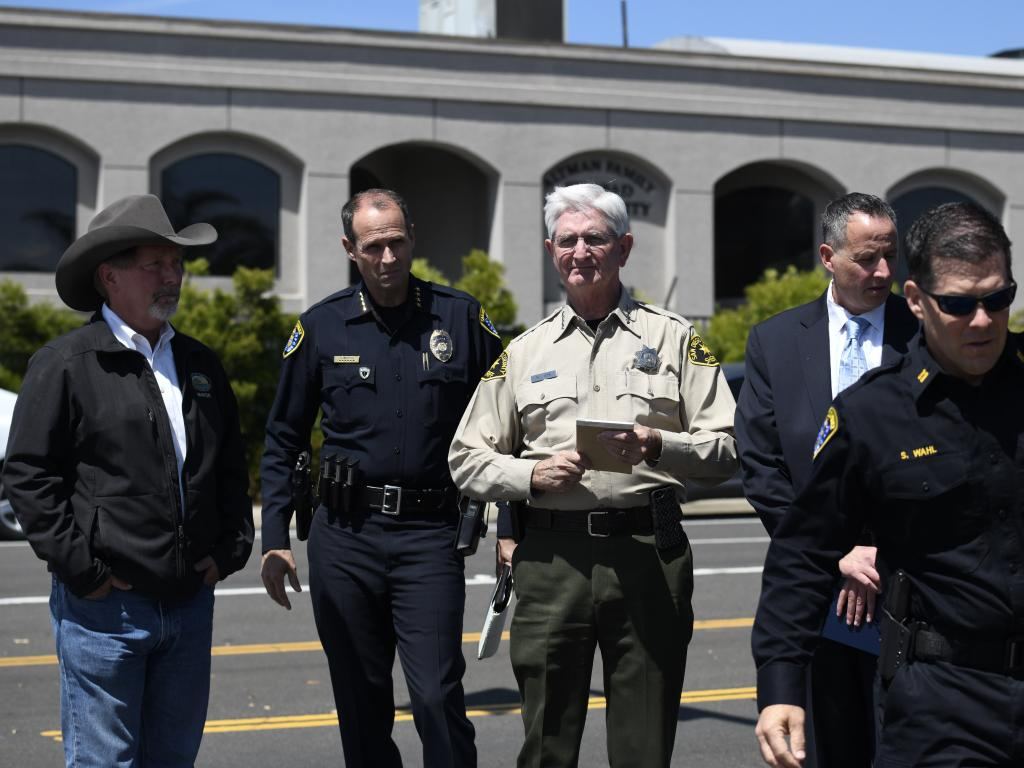 San Diego County Sheriff Bill Gore, centre, arrives with other law enforcement officials at the  Chabad of Poway Synagogue.