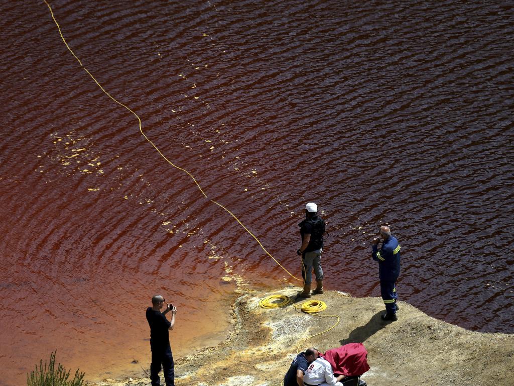 Investigators trawl for bodies in 'red lake' using specialist camera equipment. Picture: Petros Karadjias/AP