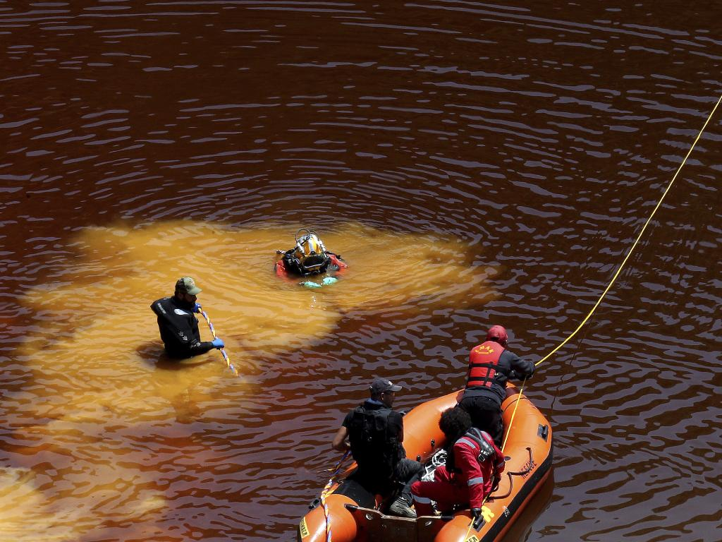 Divers retrieve a suitcase containing one of Metaxas' victims from the highly toxic Kokkinopezoula Lake near the Cyprus capital Nicosia on Sunday. Picture: Petros Karadjias/AP