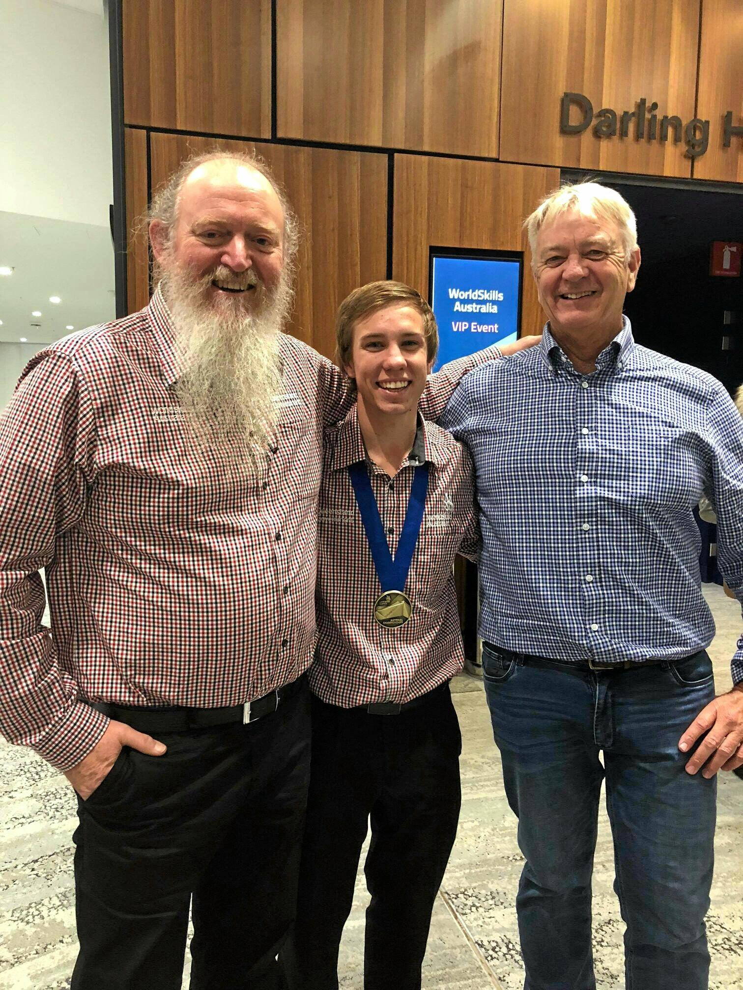 TAFE teacher and Worldskills expert Carl Balke, Pie Creek apprentice Patrick Brennan and his employer Tony Stephens celebrate Patrick's gold medal win at the national championships in Sydney.