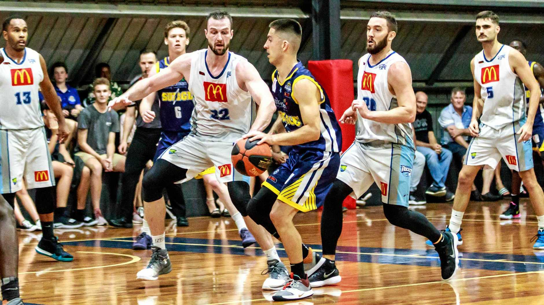 ON THE MOVE: Kyle Tipene takes on star Rockhampton Rocket NBL players Adam Gibson and AJ Ogilvy.