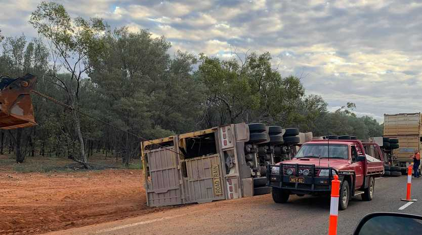 Police and council workers remained on the scene well into the afternoon, cleaning up after a road train carrying cattle rolled on the Warrego Highway.