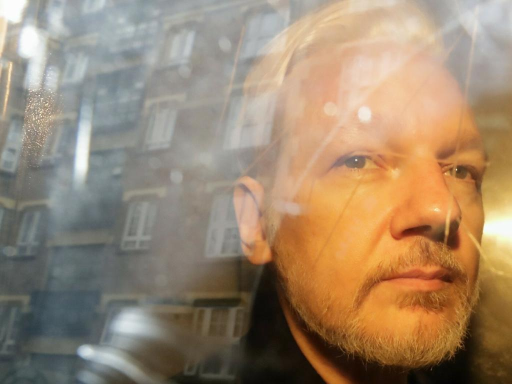 Buildings are reflected in the window as WikiLeaks founder Julian Assange is taken from court. Picture: AP