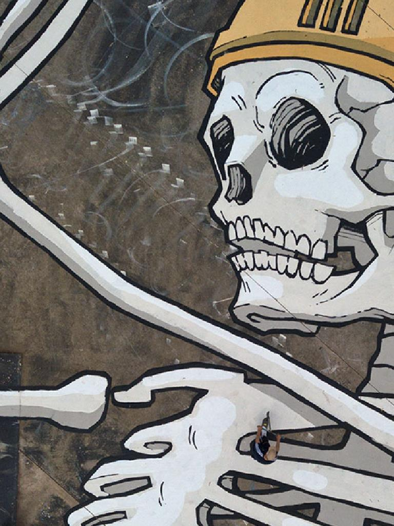 A person walks across Bennett's large skeleton mural. Picture: Kitt Bennett