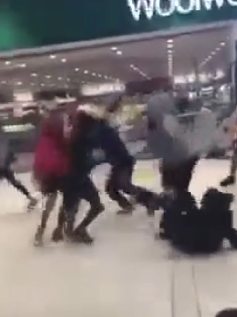 A group of teens fight outside a Woolworths.