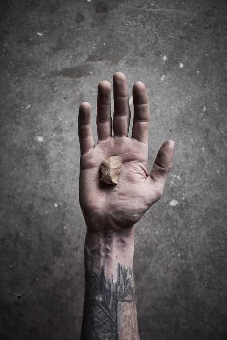 Possible title image of Dan Elbornes hand with a single ceramic stone, photography by James Green