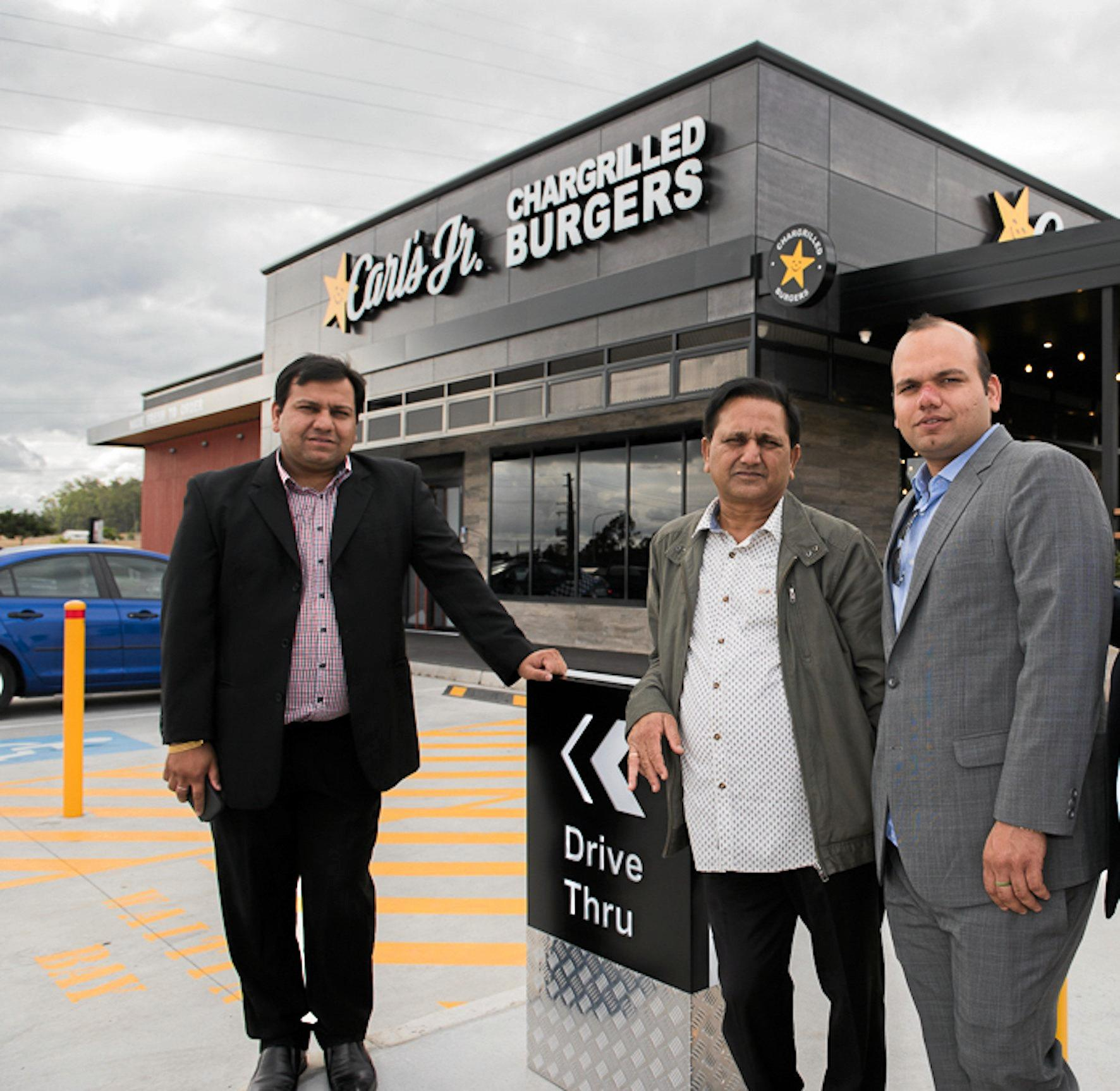 Bansal Brothers Vishal and Gaurav with their father Premnath, at the Carl's Jr store that started it all on Redbank Plains Road.
