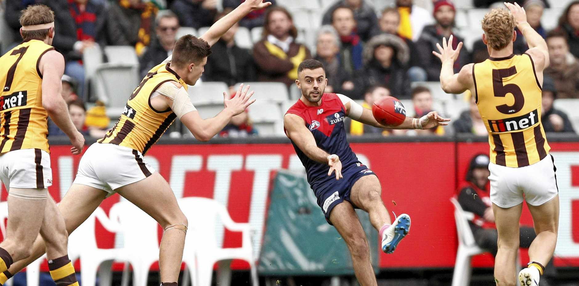 Melbourne's Christian Salem gets his kick away as the Hawks close in at the MCG on Saturday. Picture: Daniel Pockett/AAP