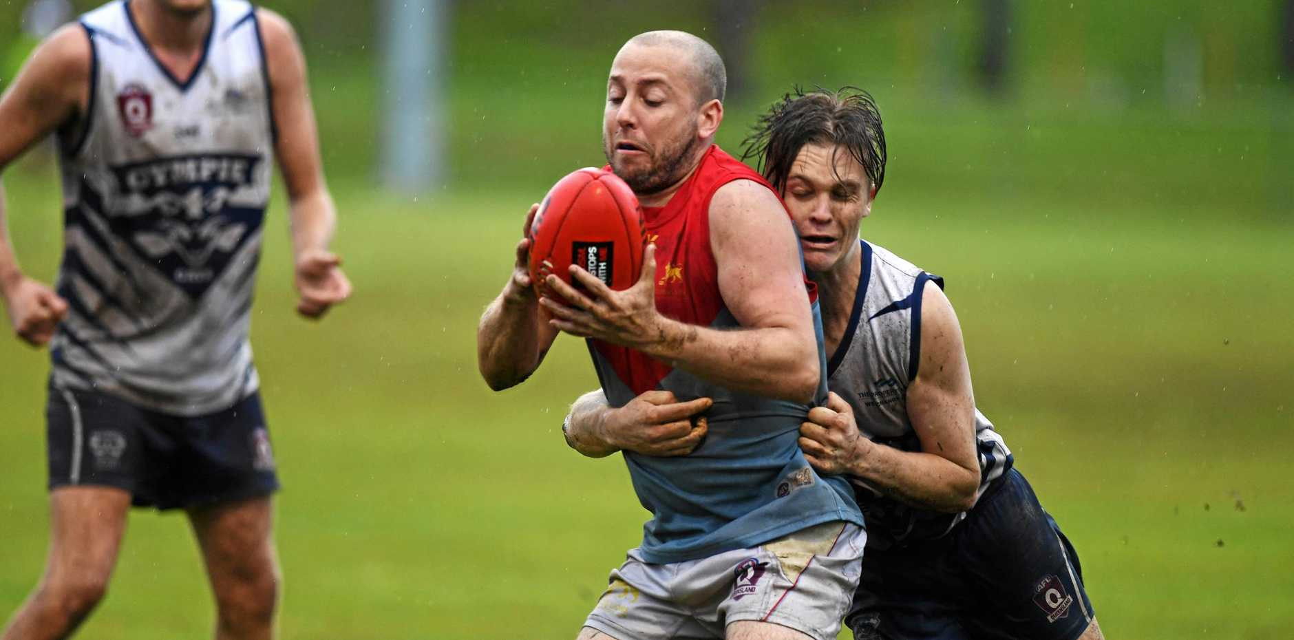 STUCK IN THE MUD: Cats defender Chris Langfeldt attempts to lay a tackle on his Kedron opponent in their 56-point loss at Ray Warren Oval last Saturday.