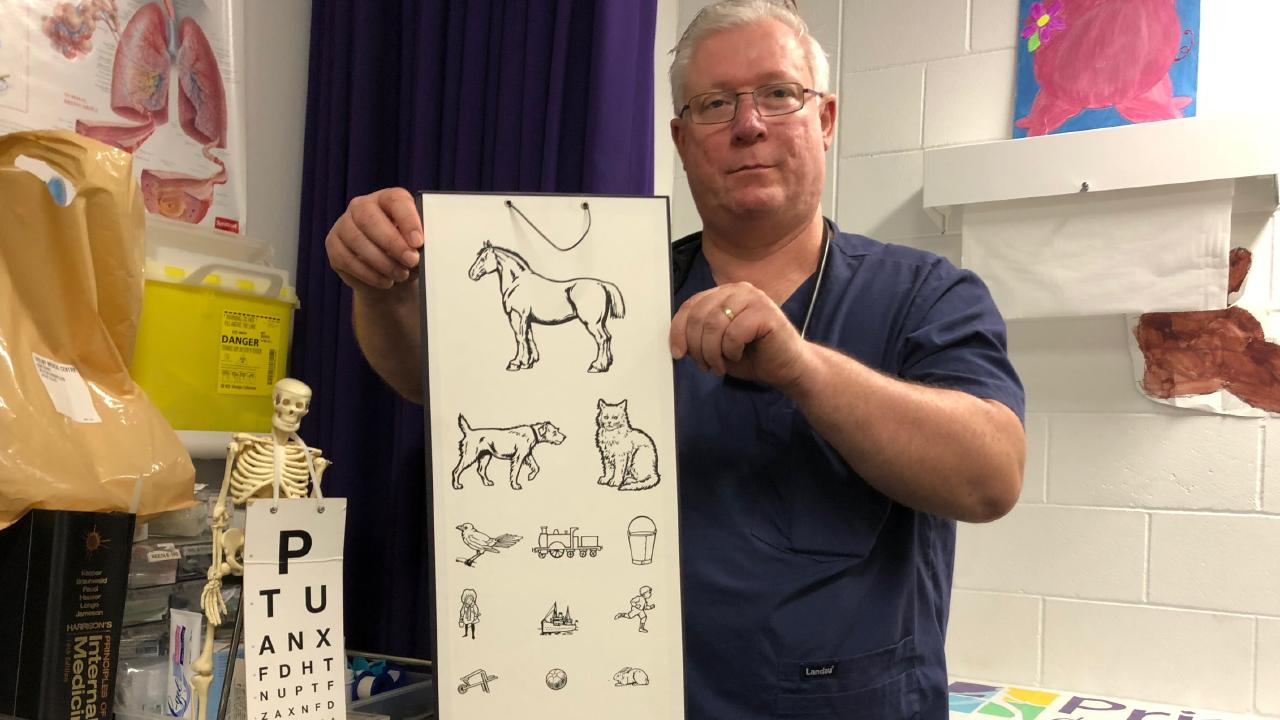 Dr Thomas Lyons with the vision chart he uses during routine eye tests.