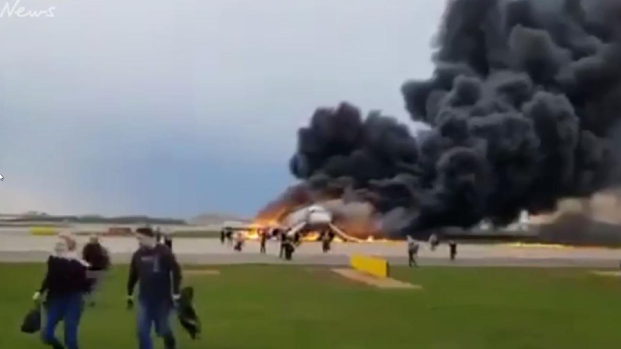 Passengers carry hand luggage off the Russian Aeroflot plane that caught fire at Moscow's Sheremetyevo International Airport.