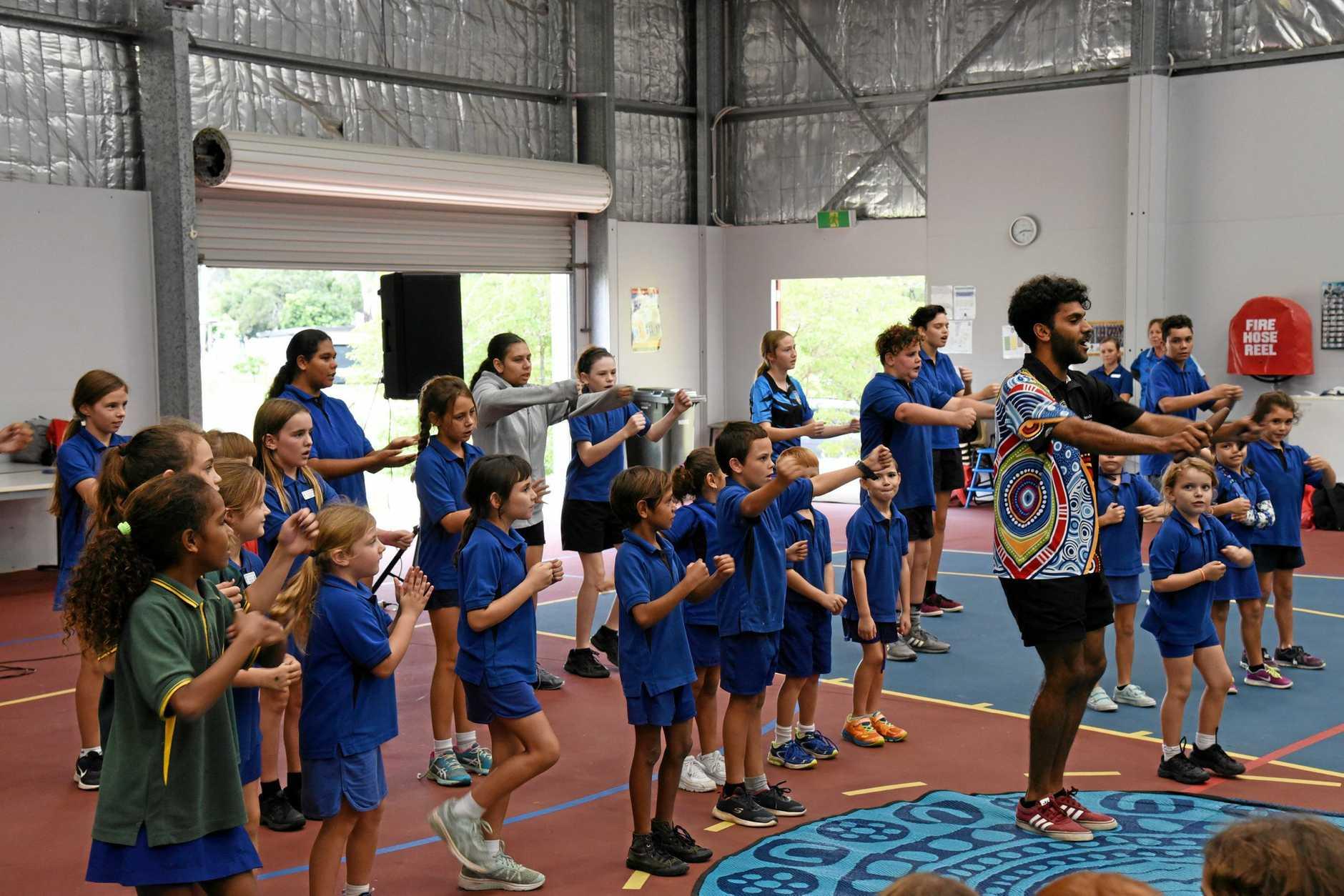 Eidsvold State School teacher aide Corey Appo leading students in Wakka Wakka farewell dance 'Gari Gynda Narmi' to see off departing principal Graeme Weatherburn.