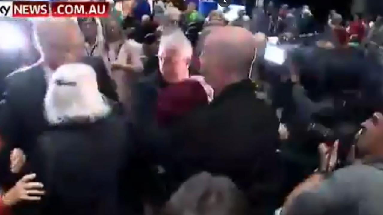 A security man gets the protesting woman into a headlock.