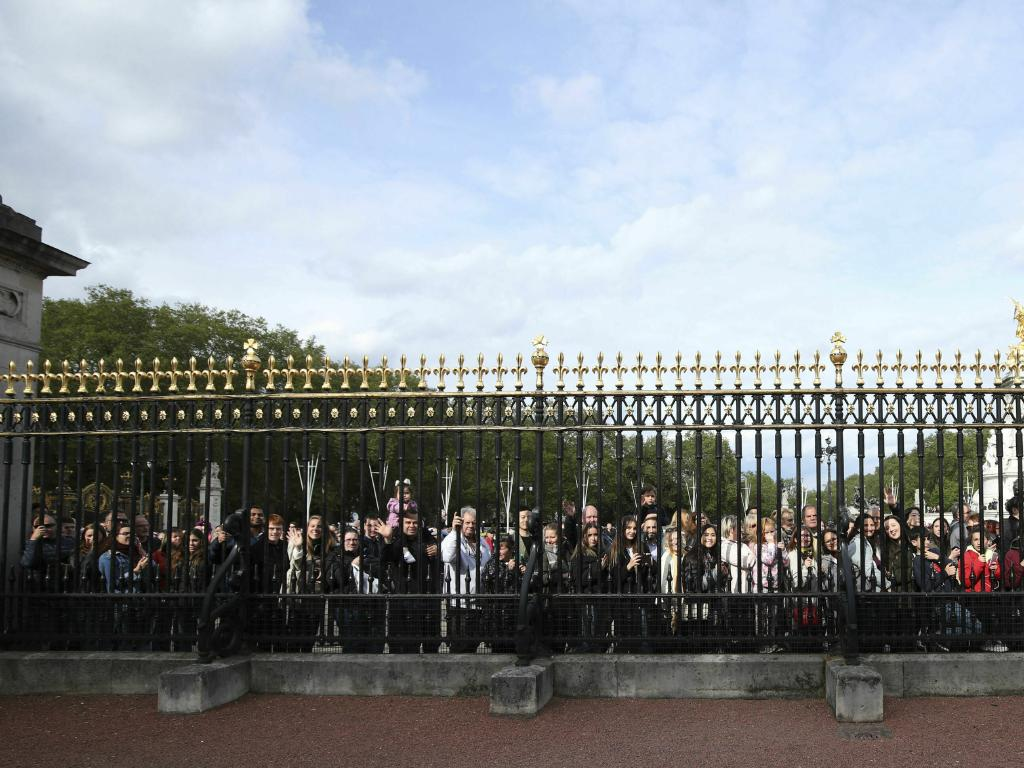 Crowds gather outside the Palace to take pictures of the historic announcement. Picture: Yui Mok/Pool Photo via AP