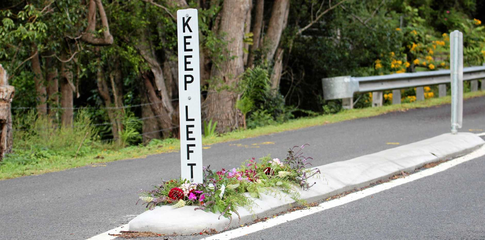 Flowers on Cecil St, Nimbin, where a woman was fatally struck by a vehicle in a hit-and-run incident overnight.