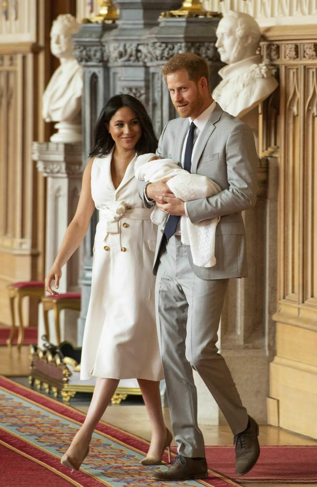 Meghan wore a white dress and Harry wore a grey suit and navy tie as they posed for their first official family photo. Picture: Dominic Lipinski/Pool via AP)