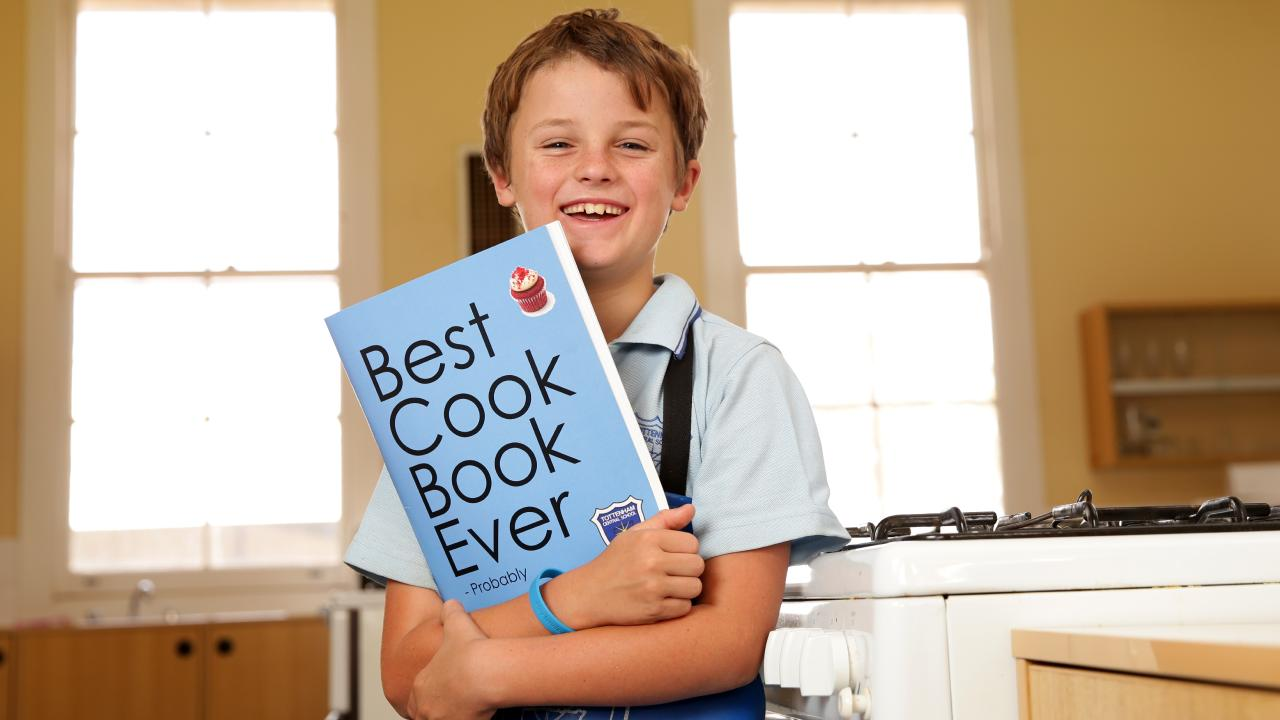 Tottenham Central School student Harry Chase, 10, pictured with the fundraising book the school came up with. Picture: Jonathan Ng