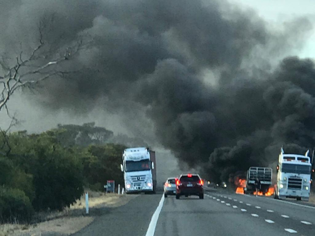 Smoke billows as tyres and the trailer burns. Picture: Patrick Clark