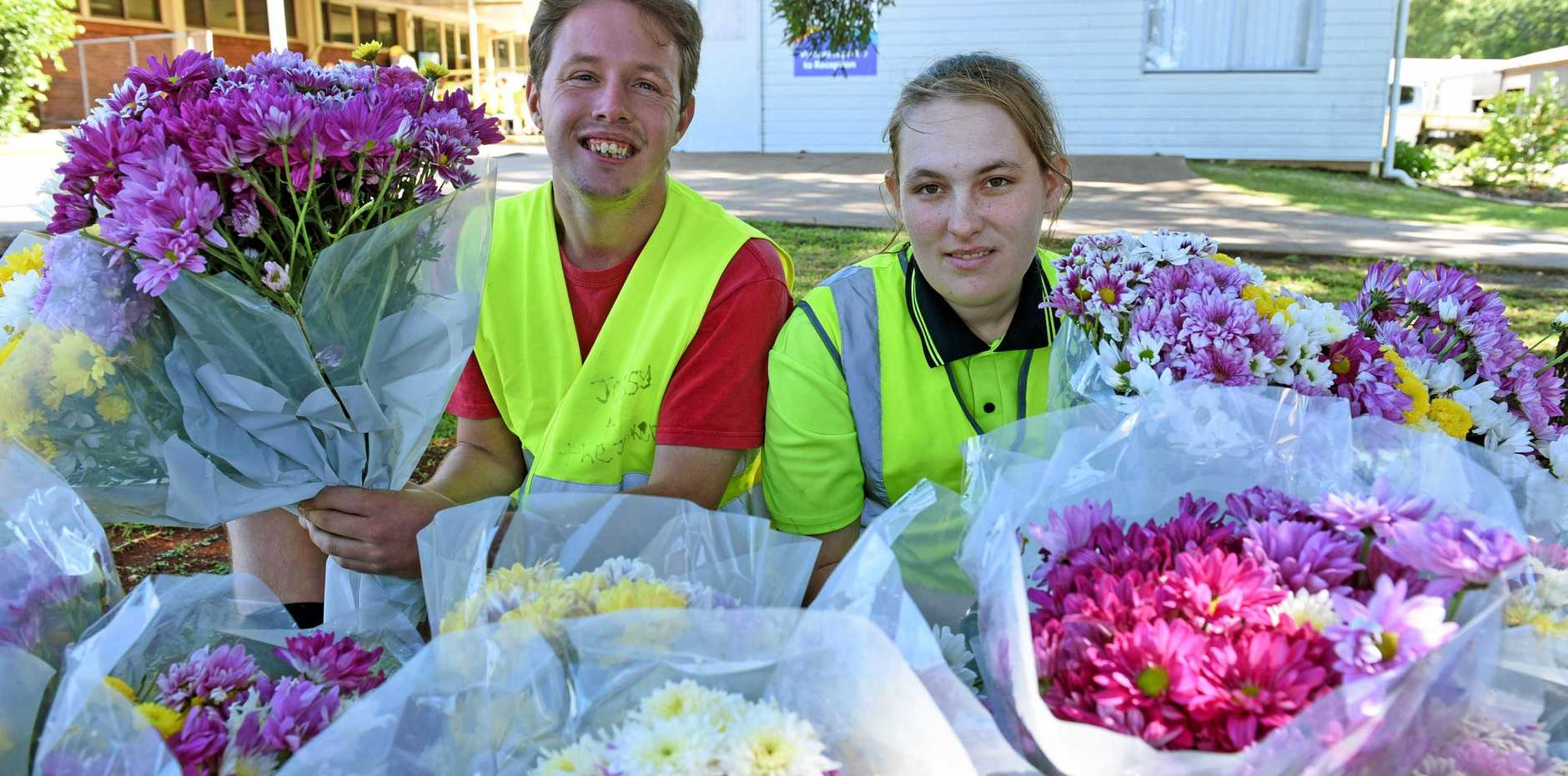 SMELL THE FLOWERS: Jessy Anderson and Jamie Lee help sell Mother's Day flowers outside the Endeavour Foundation.
