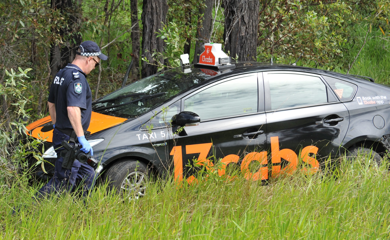 Police at the scene of a stolen crashed taxi on Three Mile Road near the Bruce Highway south of Maryborough.