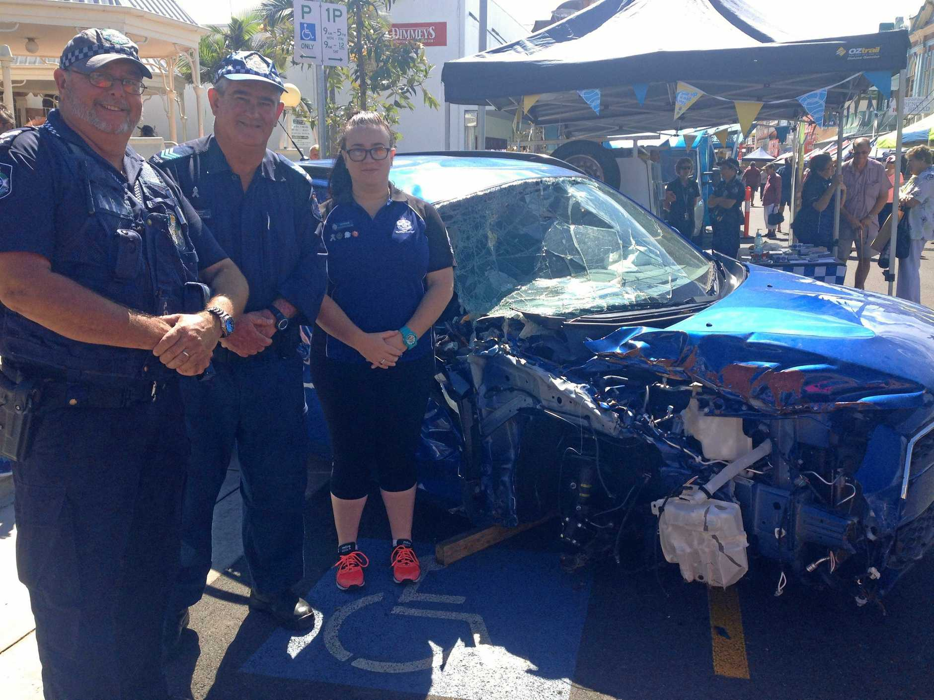 HARSH REALITY: (From left) Snr Const Adrian Edge, Sgt Steve Webb and volunteers in policing Katherine Webb in front of the crashed car in Maryborough.