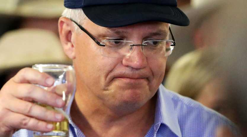 Prime Minister Scott Morrison enjoys a cold beer with locals at Gannons Pub in Julia Creek. Picture: Nigel Hallett