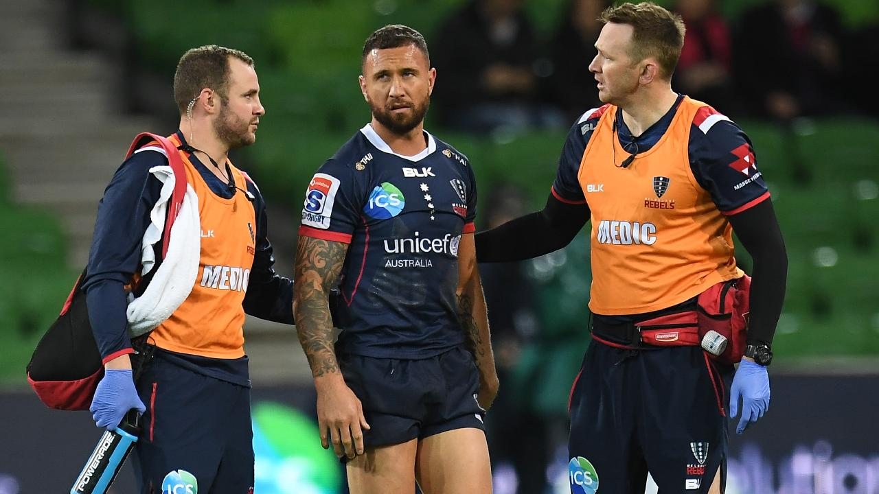 Trainers attend to Quade Cooper on Friday night. Picture: AAP
