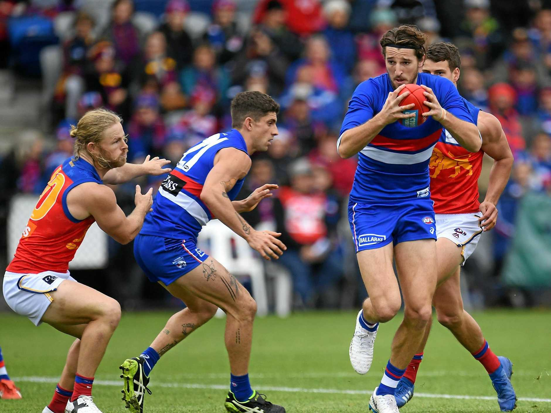 The Bulldogs' Marcus Bontempelli has possession as the Lions close in. Picture: Julian Smith/AAP