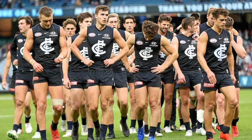 Carlton players leave the field after their devastating loss to Collingwood. Picture: Hamish Blair/AAP