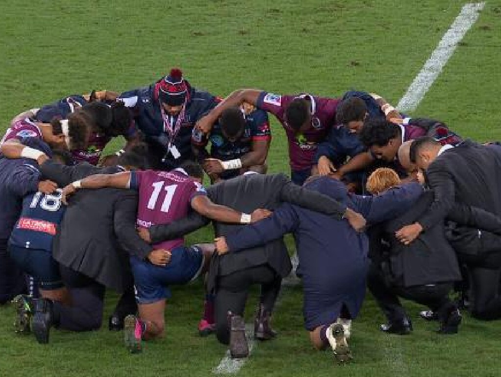 Rebels and Reds players unite in prayer.
