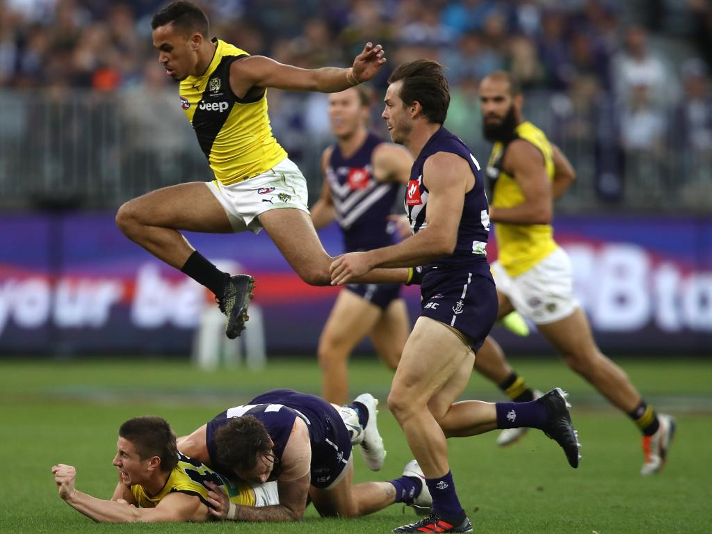 Sydney Stack of the Tigers leaps over Liam Baker and Nathan Wilson.